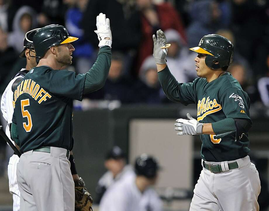 Oakland Athletics' Kevin Kouzmanoff (5) greets Kurt Suzuki after Suzuki's solo home run against the Chicago White Sox during the 10th inning of a baseball game Monday, April 11, 2011, in Chicago. Photo: Jim Prisching, AP