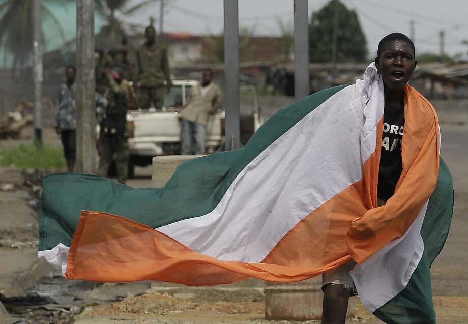 A local resident wears an Ivory Coast flag as he celebrates news of Laurent Gbagbo's capture, near soldiers allied with Alassane Ouattara, in Abidjan, Ivory Coast, Monday, April 11, 2011. The French Embassy in Ivory Coast said strongman Laurent Gbagbo wascaptured Monday by forces of democratically elected leader Alassane Ouattara. Photo: Rebecca Blackwell, AP