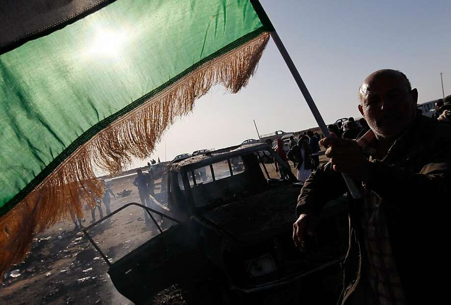 AJDABIYAH, LIBYA - APRIL 10:  A rebel soldier celebrates near the charred remains of a Libyan army loyalist pickup truck bombed by NATO forces April 10, 2011 on the outskirts of Ajdabiyah, Libya.  NATO aircraft hit the Libyan government trucks during an attack on rebels holding the strategic town of Ajdabiyah April 10, leaving behind the burned remains of at least 15 government troops. Photo: Chris Hondros, Getty Images