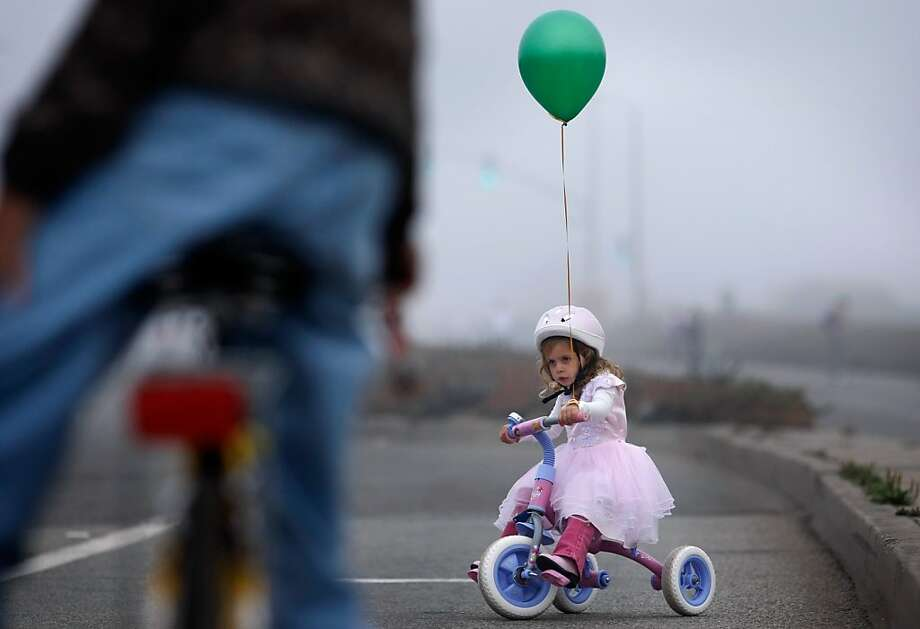 Riley Bongard, 3, pedals across the Great Highway during Sunday Streets in San Francisco. Photo: Lacy Atkins, The Chronicle