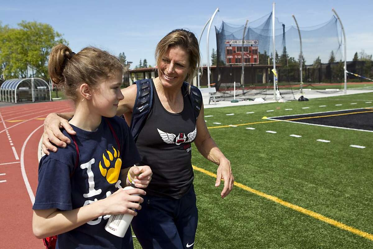 Joy Upshaw talks with her daughter Windy Margerum, age 11, after working out with a friend at Gunn High School in Palo Alto, Calif., on Wednesday, March 30, 2011. Upshaw, who just turned 50, has already set two world records in the long jump and 200 in the 50 and over age group for Master's Track.