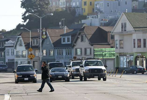 A pedestrian crosses Cesar Chavez Street as motorists wait at a stoplight on the street in San Francisco, Calif., on Thursday, January 6, 2011.  The city has unveiled a plan to remake the street with fewer traffic lanes, a new pedestrian plaza and new medium plantings. Photo: Laura Morton, Special To The Chronicle