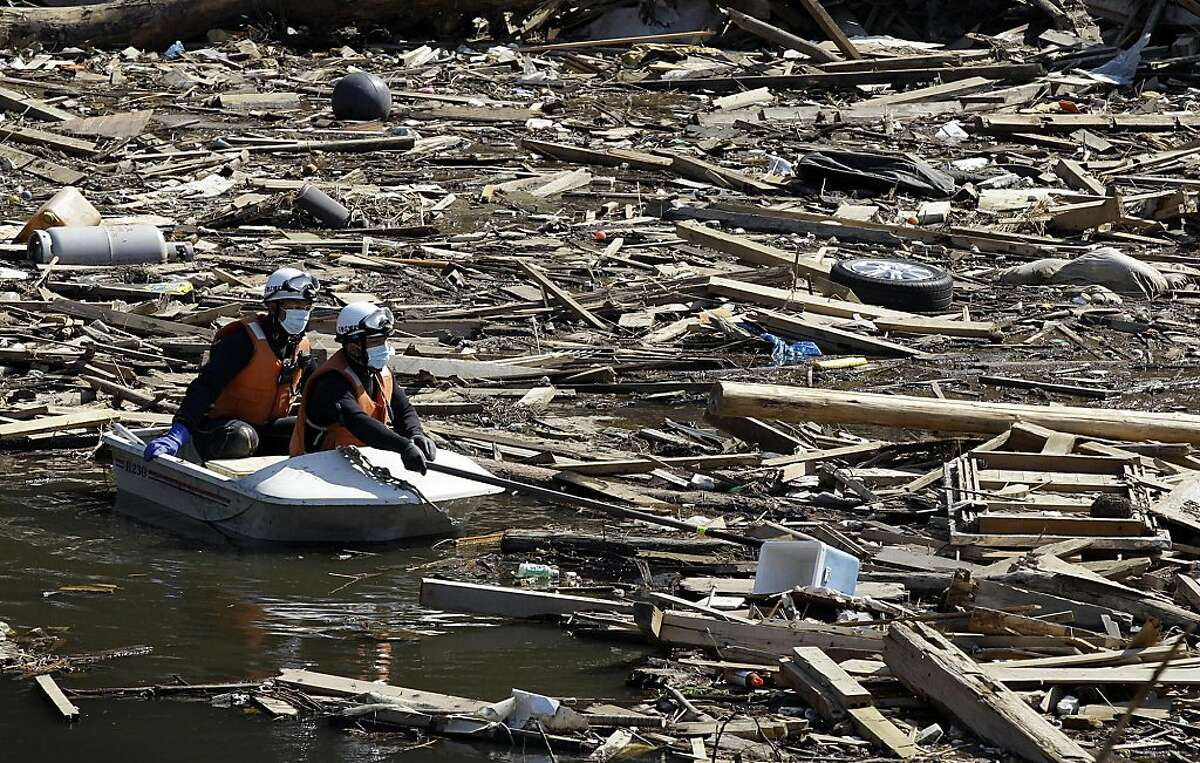 Japanese rescue team members on a boat search victims at a devastated area in Ishinomaki, Miyagi Prefecture, northeastern Japan, Tuesday, April 5, 2011, following the March 11 earthquake and tsunami.