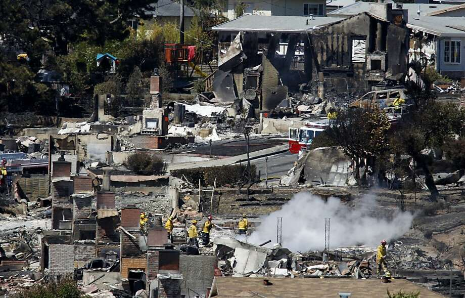 Firefighters spray water on hot spots at a home in San Bruno, Calif. on Friday, Sept. 10, 2010 thaat as destroyed after a massive natural gas pipeline explosion Thursday night. Photo: Paul Chinn, The Chronicle