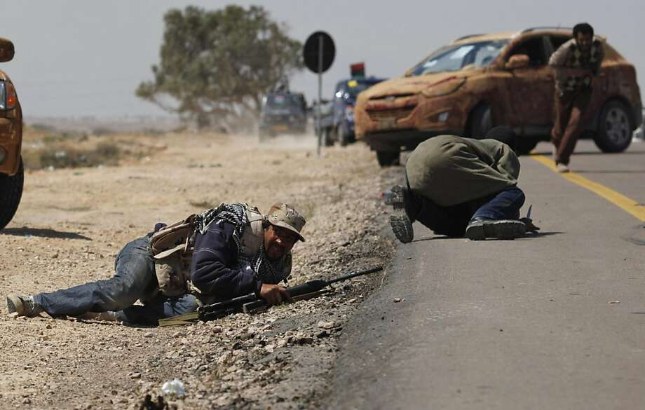 Libyan rebels duck down as others take cover as they come under attack during an exchange of fire with pro Gadhafi forces along the frontline at the outskirts of Brega, Libya Monday, April 4, 2011. Libyan rebels pushed into the strategic oil town of Bregaon Monday but came under fire from Moammar Gadhafi's forces, as a government envoy began a diplomatic push in Europe to discuss an end to the fighting. Photo: Nasser Nasser, AP