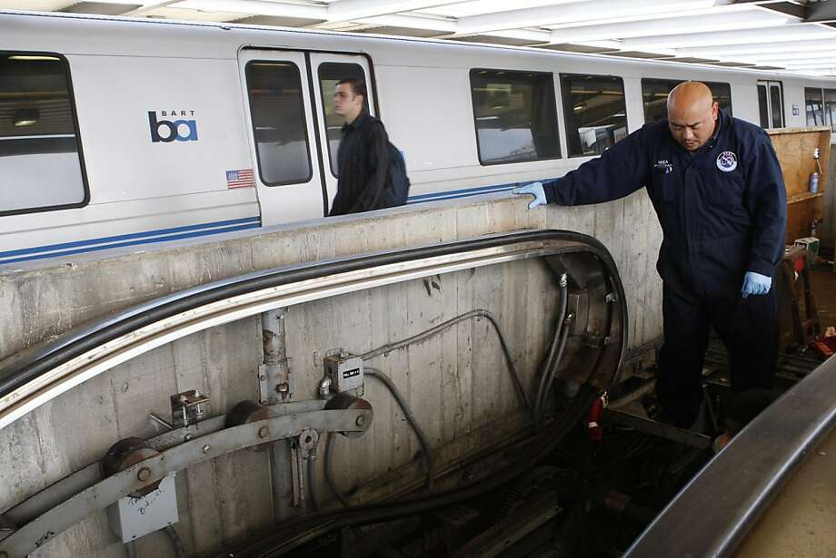 Kurt Villanueva talks to a fellow escalator maintenance worker as they attempt to repair an escalator at the Daly City BART station on Tuesday, April 5, 2011. Photo: Alex Washburn, The Chronicle