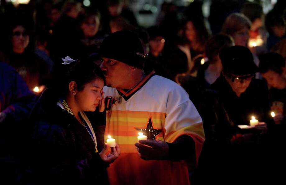 Johnie Perez comforts his daughter Macie, 12, at the vigil outside the Matagorda County Courthouse on Wednesday. Jose Avila-Alva killed himself after shooting his four children and