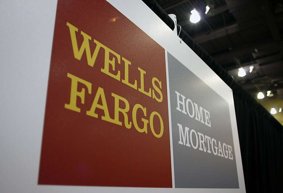 PHOENIX, AZ - MARCH 30:   A Wells Fargo sign is displayed during a home-preservation workshop at the Phoenix Convention Center March 30, 2011 in Phoenix, Arizona. People facing payment challenges on their home mortgages attended the two day event to see if they qualify for a home loan modification. A gain in the number of Americans signing contracts to buy previously owned homes in February failed to make up for the ground lost a month earlier, a sign the U.S. housing market has yet to join the economic recovery Photo: Joshua Lott, Getty Images