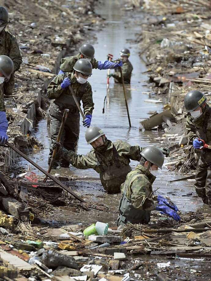 Members of Japan Self-Defense Force search missing people in Shichigahama, northeastern Japan, Monday, April 4, 2011, following the March 11 earthquake and tsunami. Photo: AP