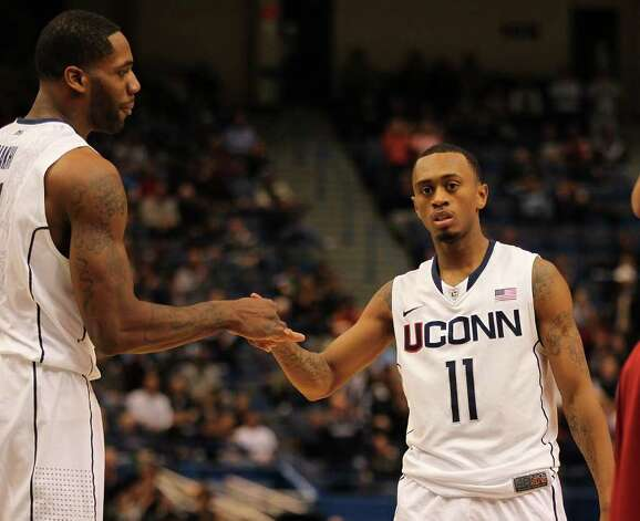 UConn's Ryan Boatright, right, is congratulated by Alex Oriakhi after a basket during Saturday's win over Arkansas. Photo: Jim Rogash/Getty / 2011 Getty Images