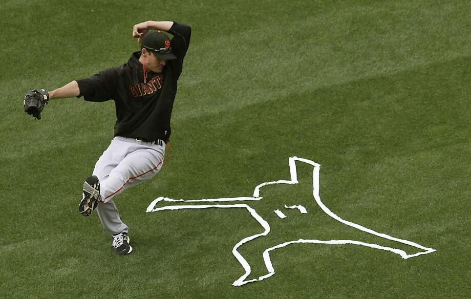 Giants pitcher Javier Lopez jokes around with the outline of Aubrey Huff, created by teammate Pat Burrell, as the San Francisco Giants prepare to play the Los Angeles Dodgers on Sunday at Dodger Stadium. The outline signified the two diving catches, one catch and one miss, that Huff went after in the eighth inning in yesterday's game. Photo: Michael Macor, The Chronicle
