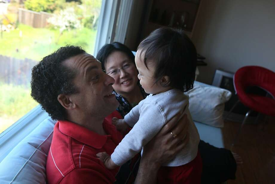 Peter Roopnarine (left) plays with his son Philip Roopnarine (right), 14 months, as Carol Tang (center) looks on as they sit on their couch in their home on Tuesday, April 2, 2011 in El Cerrito, Calif. Photo: Lea Suzuki, The Chronicle