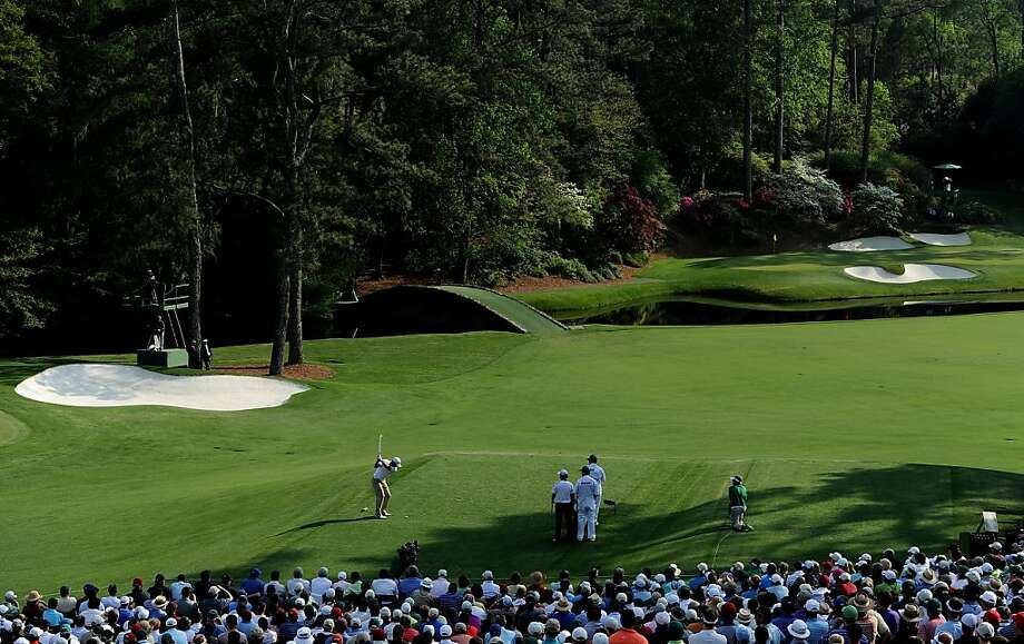 AUGUSTA, GA - APRIL 09: Jason Day of Australia hits his tee shot on the 12th hole while caddie J.P. Fitzgerald,  Rory McIlroy of Northern Ireland and caddie Colin Swatton look on during the third round of the 2011 Masters Tournament at Augusta National Golf Club on April 9, 2011 in Augusta, Georgia. Photo: Harry How, Getty Images