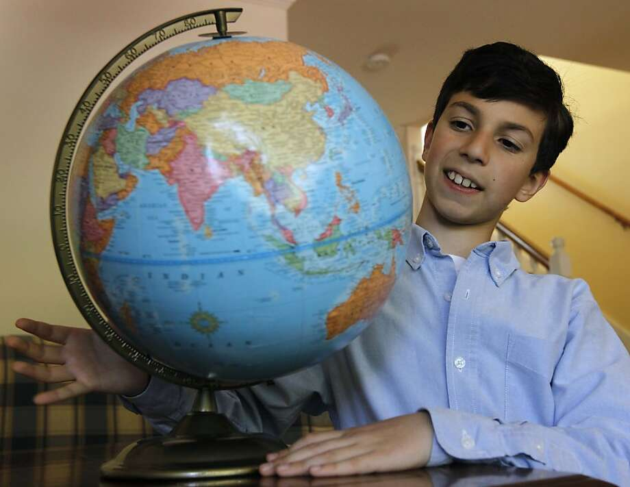 Ten-year-old Tuvya Bergson-Michelson looks at a globe at his home in San Carlos, Calif. on Saturday, April 2, 2011, after winning a statewide geography bee competition earlier this week. The globe was a gift from his great grandmother for his fourth birthday and was what first got him interested in geography. Tuvya, only the second fourth-grader to win the title, now advances to the national competition in Washington, D.C. Photo: Paul Chinn, The Chronicle