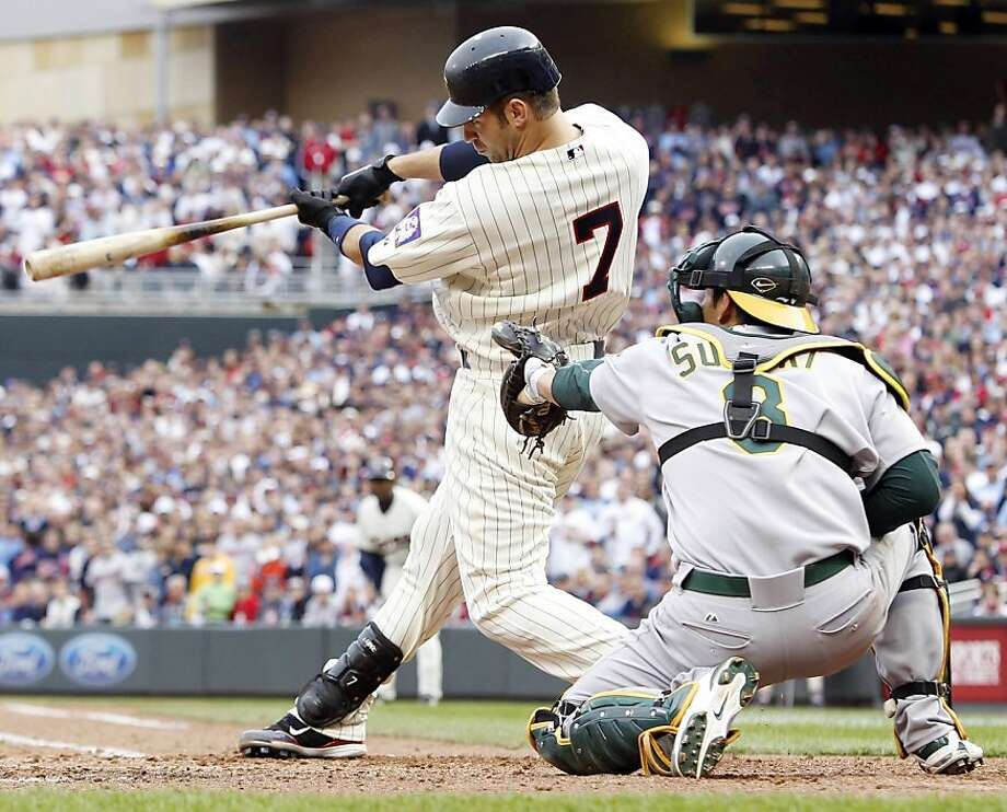 Minnesota Twins' Joe Mauer (7) hits an RBI-single to take the lead 2-1 against Oakland Athletics catcher Kurt Suzuki during the eighth inning of an MLB baseball game on Friday, April 8, 2011, in Minneapolis, Minn. The Twins defeated the Athletics 2-1. Photo: Genevieve Ross, AP