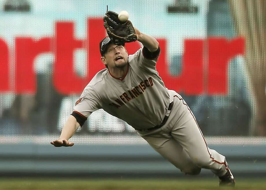 Giants right fielder Aubrey Huff makes a diving catch to rob the Dodgers' Tony Gwynn Jr. of a hit to end the seventh inning with two runners on base Saturday at Dodger Stadium. Photo: Michael Macor, The Chronicle
