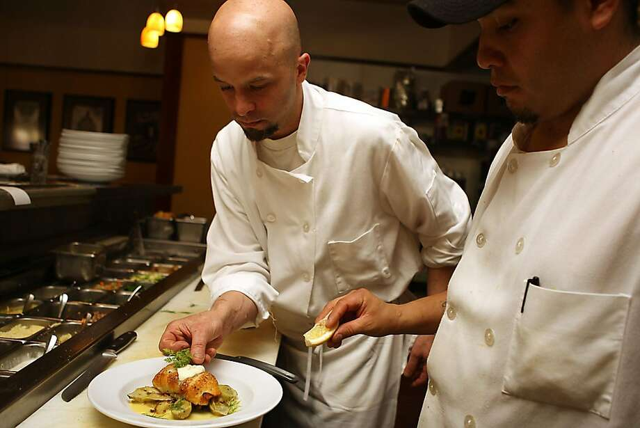 Head chef Damon Hall (right) and line cook Antonio Domguez (right) prepare pan roasted petrale sole during lunch on Friday, April 1,  in San Francisco, Calif., at MoMo's.  At MoMo's the price of seafood on the menu has been raised 10 percent to offset rising costs. Photo: Liz Hafalia, The Chronicle