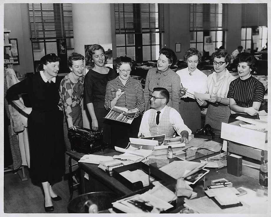 Chronicle women's section staff surrounding editor Jim Estes .. left to right, Millie Robbins, Joanne Mero Baker, Evelyn Hannay, Joan McKinney, Karola Saekel, Joan Wolfe Heil, Marian Zailian  Photo was taken: 1961. Photo: Bill Young, SF Chronicle