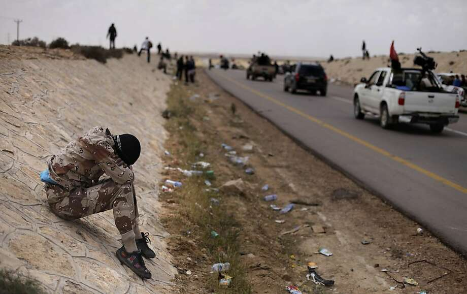 A Libyan rebel takes a break at the frontline near Brega, Libya, Saturday, April 2, 2011. NATO said on Saturday that it was investigating Libyan rebel reports that a coalition warplane had struck a rebel position that was firing into the air near the eastern front line of the battle with Gadhafi's forces. Photo: Altaf Qadri, AP