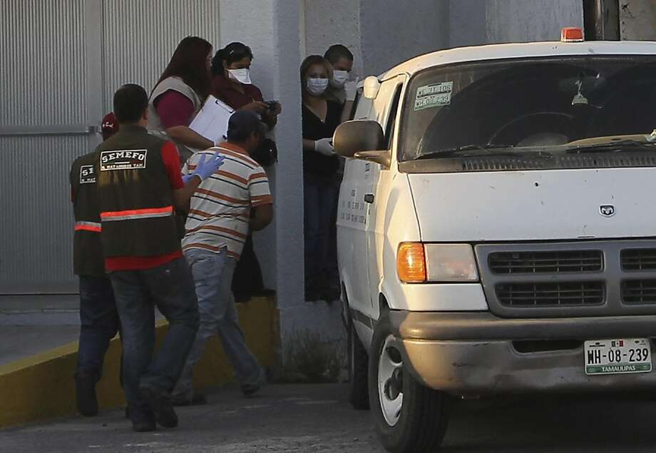 Forensic workers prepare to transfer bodies from a van into a large truck, not seen,  in the northern border city of Matamoros, Mexico Wednesday April, 6, 2011. At least fifty-nine bodies were found buried in a series of pits in the northern Mexico stateof Tamaulipas, near the site where suspected drug gang members massacred 72 migrants last summer, officials said. Photo: Rubios News, AP