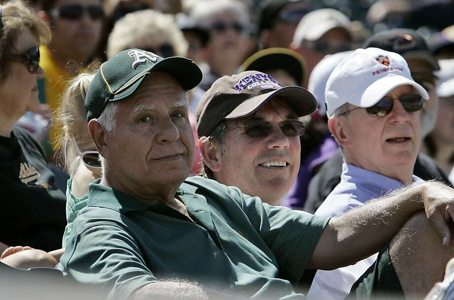 In this March 31, 2010, photo, Oakland Athletics owner and managing partner Lew Wolff, left, and general manager Billy Beane, center, watch as the Athletics played the Cincinnati Reds in a spring training baseball game in Phoenix. Wolff has been waiting two years for his old fraternity brother, commissioner Bud Selig, to tell him whether he can go ahead with his outline to move the A's from Oakland into Santa Clara County even though the San Francisco Giants hold the territorial rights in technology-richSilicon Valley. Photo: Jeff Chiu, AP