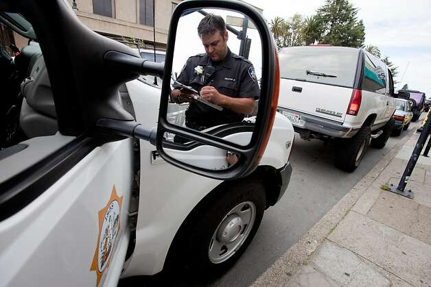 Petaluma Police Officer Burt Walker is reflected in his review mirror as he writes a ticket for cell phone violation on  Petaluma Blvd on  April 5, 2011 in Petaluma, Calif.  Photograph by David Paul Morris/Special to the Chronicle Photo: David Paul Morris, Special To The Chronicle