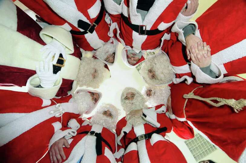 Men, most of them students and retirees, are dressed as Santa Claus as they pose together in the job