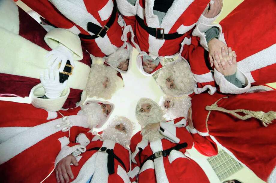 Men, most of them students and retirees, are dressed as Santa Claus as they pose together in the jobless center in Rostock, eastern Germany Wednesday Dec. 7, 2011. Many people take part time jobs as Santas these days to make some extra money. Photo: Frank Hormann, Associated Press / dapd