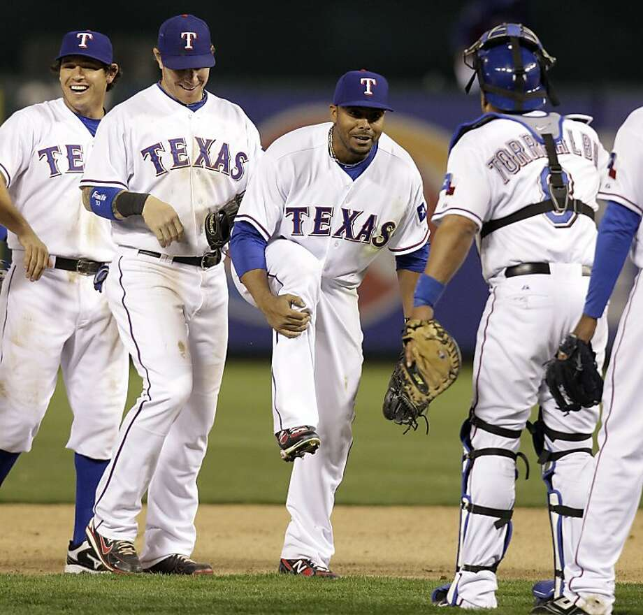 Texas Rangers' Nelson Cruz, center, holds his right leg as he jokes with catcher Yorvit Torrealba, right, as Ian Kinsler, left, and Josh Hamilton look on following a baseball game against the Seattle Mariners on Monday, April 4, 2011, in Arlington, Texas.The Rangers won 6-4. Photo: Tony Gutierrez, AP