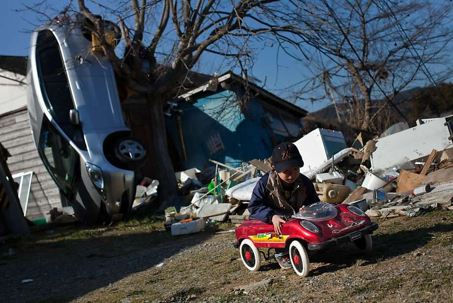 A boy that survived the tsunami plays in a toy car in front of a real car still balancing on its front end after being washed up by the March 11 tsunami triggered by a 9.0-magnitude earthquake in Ishinomaki, Miyagi prefecture, on April 6, 2011. With the toll topping 10,000 confirmed dead the March 11 quake has become Japan's deadliest natural disaster since the 1923 Great Kanto Earthquake, which killed more than 142,000 people. Hundreds of thousands of people have been displaced from their homes and havetaken shelter in emergency facilities. Photo: Yasuyoshi Chiba, AFP/Getty Images