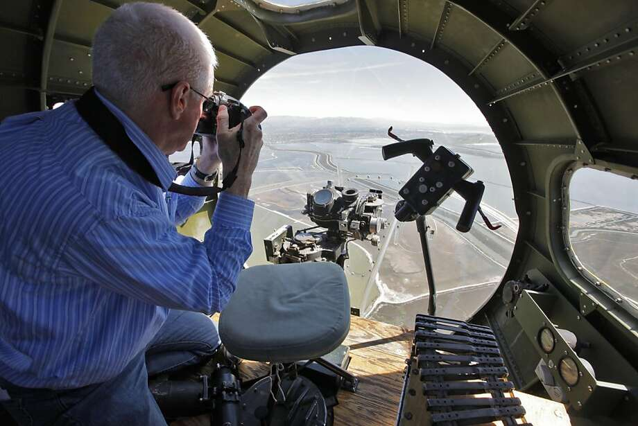 Members of the media take pictures from one of the WWII Boeing B-17 Fighter,  gunner positions as they fly over the Oakland Estuary,  Monday April 4, 2011, to promote the public tours and rides that will be available  this weekend in Hayward, Calif. Photo: Lacy Atkins, The Chronicle