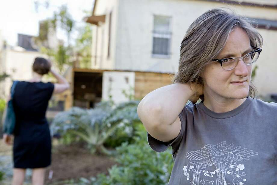 Author, farmer and Ghost Town Farm blogger, Novella Carpenter, right, in her backyard farm in Oakland, Calif. on Wednesday, March 30, 2011.  Although Carpenter, cancelled her usual Wednesday Farmstand several people who read her blog, Ghost Town Farm, including Anne Shaver, left, showed up to see the urban farm. Kat Wade / Special to the Chronicle Photo: Kat Wade, Special To The Chronicle