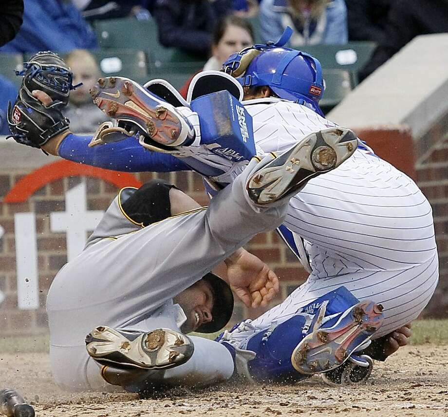 Pittsburgh Pirates' Neil Walker, left, collides with Chicago Cubs catcher Geovany Soto while scoring a run during the ninth inning of a baseball game Sunday, April 3, 2011, in Chicago. Walker scored the go-ahead run in the Pirates' 5-4 win. Photo: Charles Rex Arbogast, AP