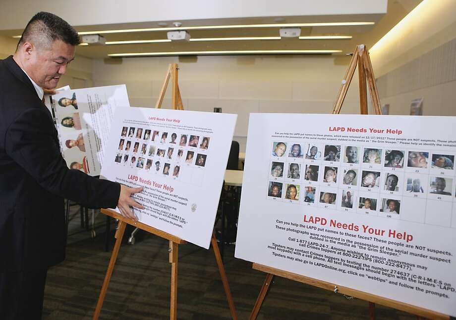 Los Angeles Police Officer Gregory Baek  sets photos of unidentified women they believe may be linked to Lonnie Franklin Jr., the Grim Reaper serial killer, during a news conference in Los Angeles Tuesday, April 5, 2011. Photo: Damian Dovarganes, AP