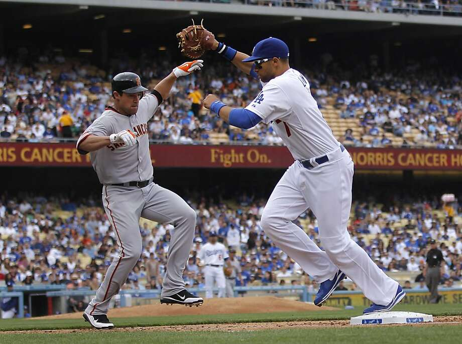 Los Angeles Dodgers first baseman James Loney, right, fields the throw to force out San Francisco Giants' Pat Burrell at first base during the fourth inning of a baseball game in Los Angeles, Saturday, April 2, 2011. Photo: Jae C. Hong, AP