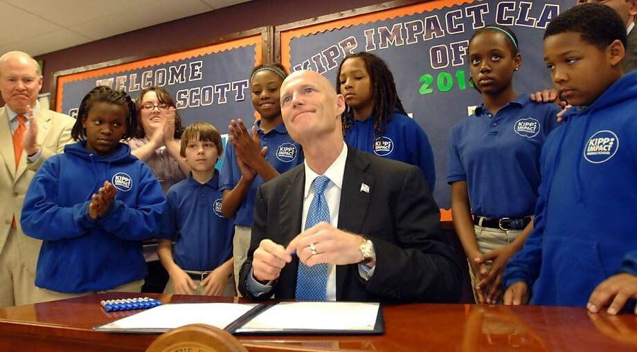 Florida Gov. Rick Scott signs his first bill surrounded by students of the Kipp Middle School, Thursday, March 24, 2011, in Jacksonville, Fla. Far-reaching but divisive legislation that creates a merit pay plan tied to student test scores for Florida teachers while ending tenure for new hires became law Thursday with Scott's signature. Photo: Don Burk, AP