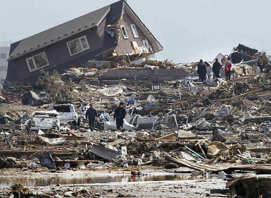 People walk in the rubble in Minamisanriku town, Miyagi Prefecture, northern Japan, Sunday, March 13, 2011, two days after a powerful earthquake-triggered tsunami hit the country's east coast. (AP Photo/The Yumiuri Shimbun) JAPAN OUT, CREDIT MANDATORY Photo: The Yumiuri Shimbun, Associated Press