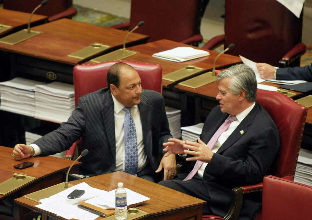 New York Senate Majority Leader, Dean Skelos, R-Rockville Centre, right, and Deputy Minority Leader Sen. Tom Libous, R-Binghamton speak in the Senate chamber at the Capitol in Albany, N.Y., on Wednesday, Dec. 7, 2011. New York's Legislature is expected today to vote on a major agreement between Gov. Andrew Cuomo and legislative leaders that will increase the income tax on the wealthiest residents while providing a tax break for the middle class. (AP Photo/Hans Pennink)