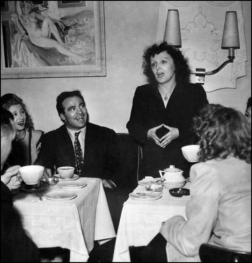 PARIS - 1947: Singer Edith Piaf is surrounded by her friends, including middleweight boxing champion Marcel Cerdan (L), whom she was having an affair with, sings one of her many successes at a caf? table in Paris circa 1947. Photo: AFP/Getty Images