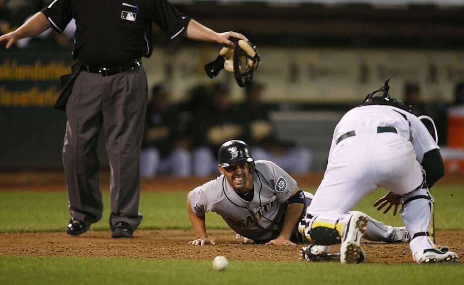 Ja Wilson of the Seattle Mariners takes a look at the loose ball that failed to get him out at home plate during the top of the ninth inning against the Oakland Athletics at the Oakland-Alameda County Coliseum  on Saturday, April 2, 2011. Photo: Alex Washburn, The Chronicle