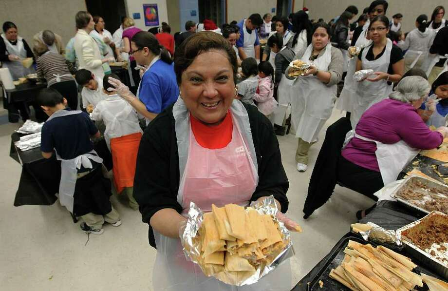 Christina Vasquez (center) was amongst the 1,300 volunteers who helped make thousands of tamales at Lanier High School for a record-setting tamalada on Wednesday, Dec. 7, 2011. Vasquez's daughter, Victoria, attends the culinary magnet program at Lanier. Organizers said about 1,100 students and 200 neighborhood volunteers gathered at the school to make tamales and to attempt to set a record for the most made by weight. In the end, they achieved the goal of 17,232 tamales weighing in at 2,420.9 pounds. The achievement will now be sent off to Guiness Book of World Records to be certified. Photo: KIN MAN HUI, ~ / SAN ANTONIO EXPRESS-NEWS