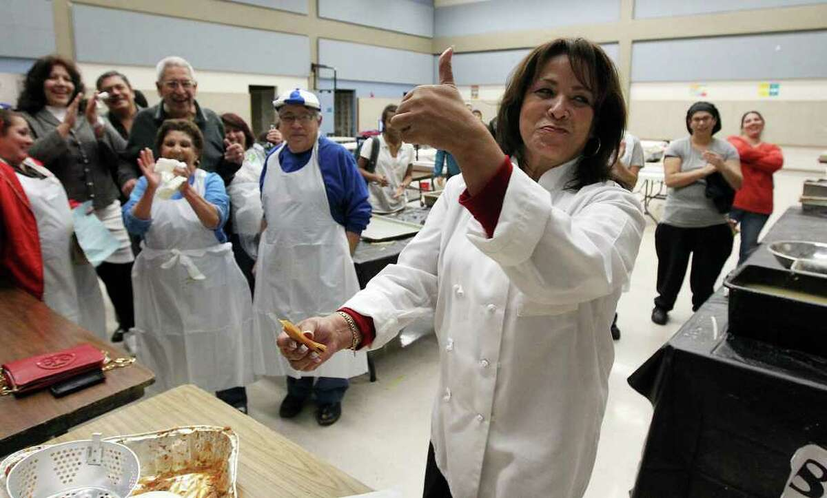 Tamale expert Oralia Salame (front) gives the thumbs-up after sampling a tamale at Lanier High School at the conclusion of a record-setting tamalada on Wednesday, Dec. 7, 2011. Organizers said about 1,100 students and 200 neighborhood volunteers gathered at the school to make tamales and to attempt to set a record for the most made by weight. In the end, they achieved the goal of 17,232 tamales weighing in at 2,420.9 pounds. The achievement will now be sent off to Guiness Book of World Records to be certified. Kin Man Hui/kmhui@express-news.net