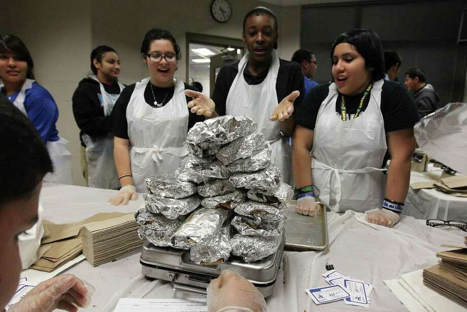 December 2011: Irving Middle School students Baby Garcia (from left), Isaiah Robinson and Ashley Ybarra marvel at the amount of tamales they made at Lanier High School at a record-setting tamalada. Organizers said about 1,100 students and 200 neighborhood volunteers made 17,232 tamales weighing in at 2,420.9 pounds — an achievement that was certified by the Guinness Book of World Records. Photo: KIN MAN HUI, ~ / SAN ANTONIO EXPRESS-NEWS