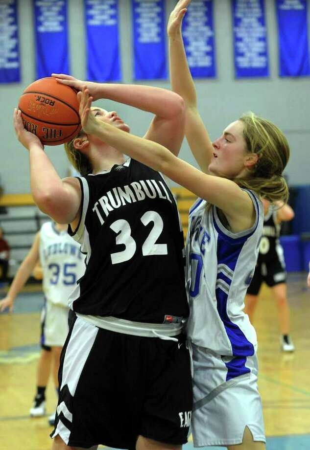 Trumbull's #32 Erin Moore, left, looks to make a shot under the basket as Fairfield Ludlowe's #30 Pauline Blatt tries to block, during girls basketball action in Fairfield, Conn. on Wednesday December 7, 2011. Photo: Christian Abraham / Connecticut Post