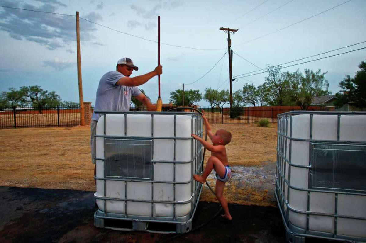 Brennen Hood, 3, tries to help his father, Aaron Hood, school superintendent and athletic director for Robert Lee High School, as he cleans out large chemical containers which will be used as water hauling tanks, at his home. Each tank holds nearly 250 gallons of water and residents of Robert Lee are forced to drive to neighboring cities to find water to be used for watering lawns and trees.