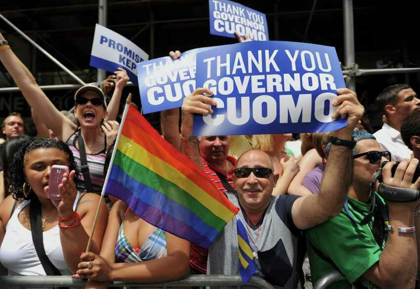 People hold signs thanking Gov. Andrew Cuomo during the New York City gay pride march June 26. After that landmark decision, the state could do more to improve the rights of transgender people, advocates say. (Stan Honda/AFP/Getty Images)