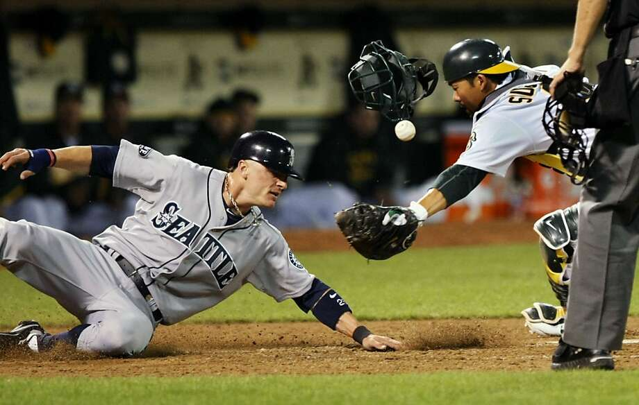 The Seattle Mariners' Brendan Ryan slides under A's catcher Kurt Suzuki's tag for the first of two runs scored in the sixth inning of the A's home opener in Oakland on Friday. Photo: Lance Iversen, The Chronicle