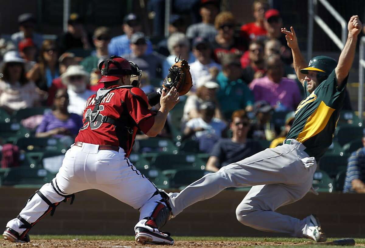 Kevin Kouzmanoff beats the tag by catcher Miguel Montero to score on Mark Ellis' single during the 6th inning, when Oakland scored eight runs, in the A's spring training baseball game against the Arizona Diamondbacks at Salt River Fields in Scottsdale, Ariz. on Thursday, March 24, 2011.