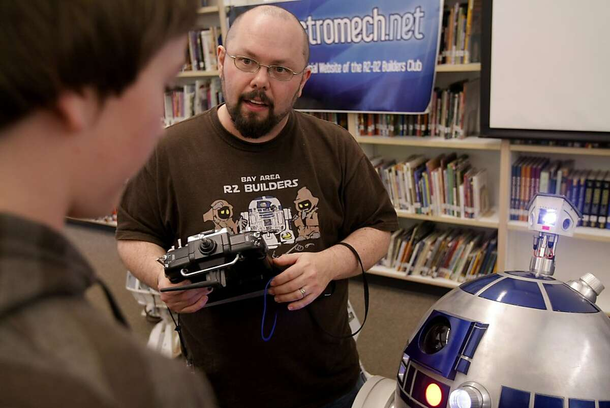 Chris James explains the workings of his R2-D2 droid to a student of River Charter School on March 11, 2011.
