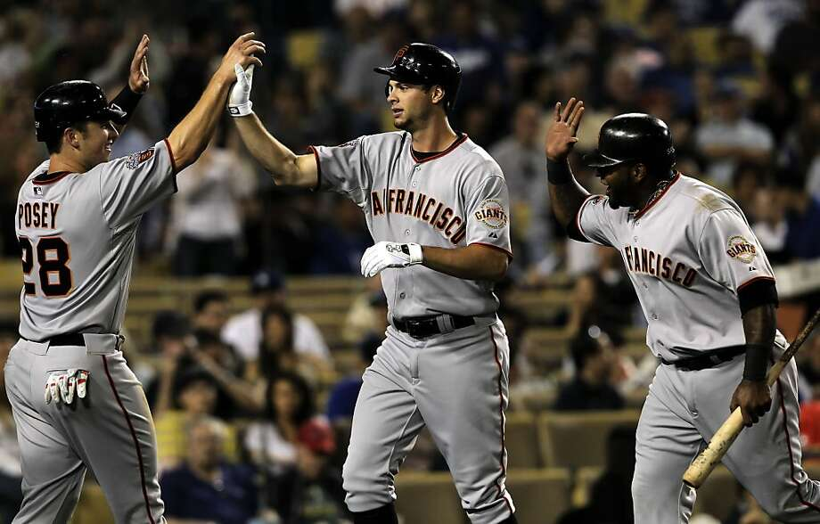 Giants rookie Brandon Belt (center) gets high fives from Buster Posey (left) and Pablo Sandoval after Belt's three-run homer to center in the fourth inning against the Los Angeles Dodgers on Friday at Dodger Stadium. Photo: Michael Macor, The Chronicle